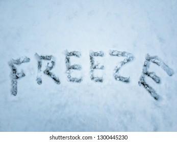 FREEZE written in the freshly fallen snow.