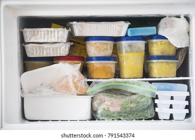 a freezer packed with chicken, soup and various frozen food