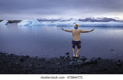Freezing brave man at Jokulsarlon glacier lagoon is ready to jump into the freezing water, where the ice blocks are shining like diamonds, Jokulsarlon, Iceland