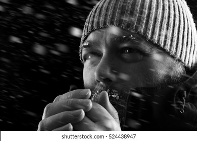 Freezing cold man standing in a snow storm blizzard trying to keep warm. Wearing a beanie hat and winter coat with frost and ice on his beard and eyebrows. Black and white.