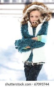 Freezing cold seven year old girl standing in snow storm without coat.