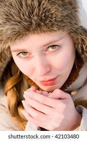 freezing girl warms his hands breath
