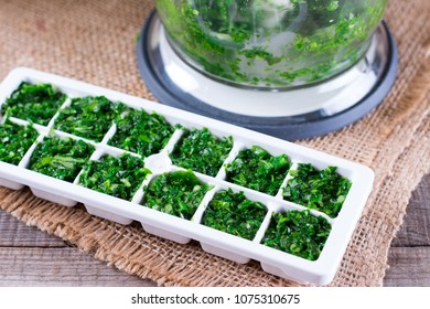 freezing greens in ice cube mould on a wooden table