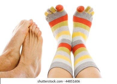 Freezing naked feet of a man and a woman 's feet with warm socks isolated on white - abstract illustration of cold, of freezing.
