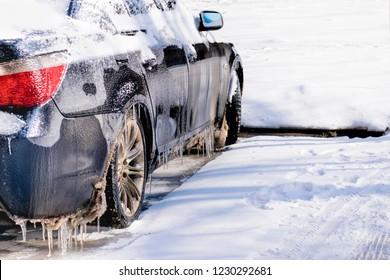 Freezing rain ice coated car.Bad driving weather in freezing rain.Black vehicle car covered in freezing rain
