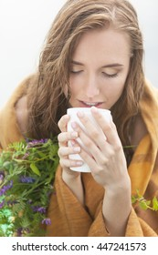 Freezing and wet woman in plaid enjoying tea with herbs