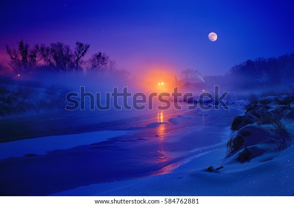 In freezing winter night full moon illuminates the river is covered with with ice, snow and fog.