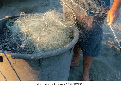 Fregene, Italy - September 29, 2019: Untangling the net. Fishermen pulling and mending the traditional fishing nets by hand