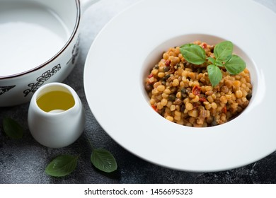 Fregola pasta with bell pepper, capers, green basil and olive oil, studio shot