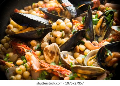 Fregula with seafood, traditional Sardinian recipe with durum wheat semolina and mixed seafood