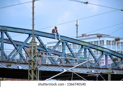 """Freiburg, BW / Germany - April 11 2019"" - Man sitting on metal bridge"