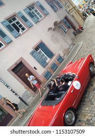FREIBURG, GERMANY - AUGUST 3, 2018: A cat looks on as a 1959 Alfa Romeo 2000 Touring Spider approaches the finish line at the Schauinsland Klassik 2018 classic car rally.