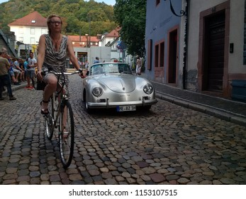 FREIBURG, GERMANY - AUGUST 3, 2018: A 1959 Porsche 356 A Cabriolet approaches the finish line at the Schauinsland Klassik 2018 classic car rally as a woman cycles past.