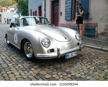 FREIBURG, GERMANY - AUGUST 3, 2018: A 1959 Porsche 356 A Cabriolet approaches the finish line at the Schauinsland Klassik 2018 classic car rally as a young woman looks on.