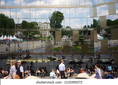 FREIBURG, GERMANY - JUNE 29, 2018: The city of Freiburg and people on a terrace reflected in the modern glass facade of the University Library of Freiburg Im Breisgau, Germany