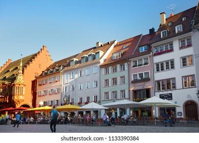 FREIBURG IM BREISGAU, GERMANY - JUNE 19, 2018: Tourists and locals enjoying a sunny evening at the central square of Freiburg Munsterplatz in Freiburg, Baden-Wurttemberg, Germany
