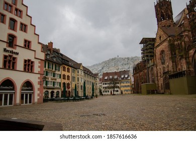 Freiburg im Breisgau/Germany - 10 28 2012: the main square of Freiburg - Munsterplatz and buildings on it, Trade house, Munster cafedral. Black forest in snow on the backround