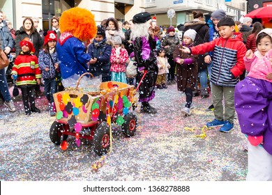 Freie Strasse, Basel, Switzerland - March 12th, 2019. A small colorful decorated carnival cart on a confetti covered street