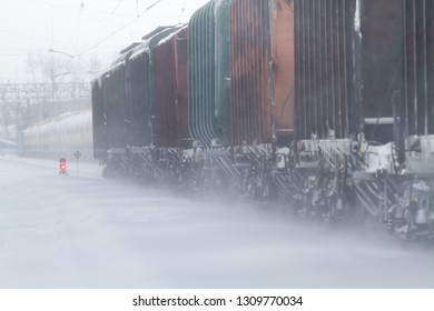 freight cars go by rail in winter in a snowstorm