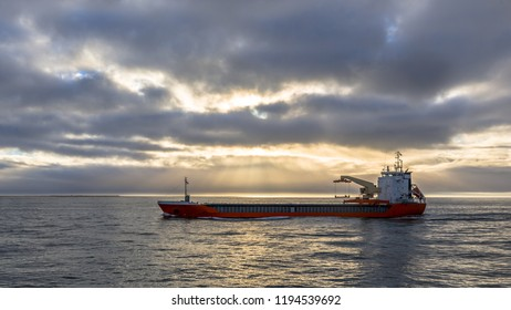 Freight ship on the North Sea under dramatic clouded sky just before sunset