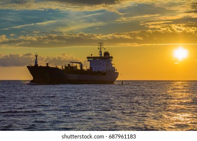freight ship on sunset light going to port in Riga,Latvia, industrial transportation background