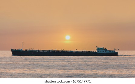 Freight ship passing The Markermeer lake in Holland during sunset