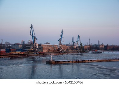 Freight shipping containers and gas oil tanks at the docks. in import export and business logistic. Cargo ship docked at at the port. Cargo cranes by winter evening in the Port Riga, Latvia.