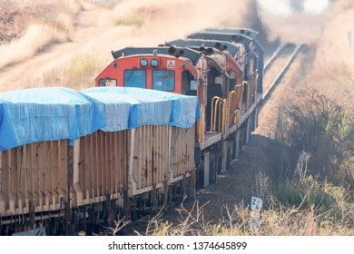 Freight train with covered carriages going through a cutting