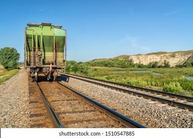 freight train with covered hopper cars to transport grain is running through Nebraska Sandhills