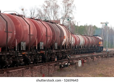 Freight train with fuel passing the station in the middle of the woods
