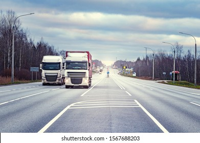 Freight trucks move fast on the highway at sunset time.