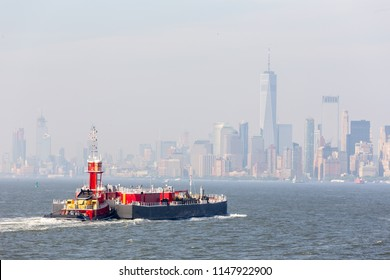 Freight tug pushing cargo ship to the port in New York City and Lower Manhattan skyscarpers skyline in background. New York City, USA.