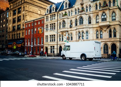 Freight van for transportation goods for delivery service moving on avenue in downtown, white truck automobile body with copy space area for advertising content or commercial information on street