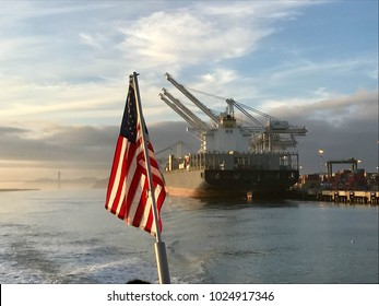 Freighter ship with dock cranes in background and American flag in foreground at sunset