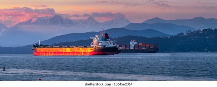 freighters stop at the bay of vancouver at sunset.