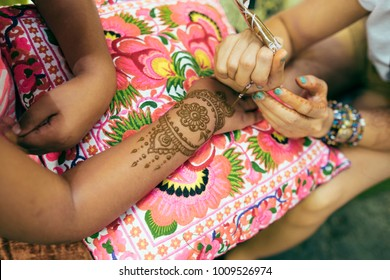 Fremantle, Perth, Australia - Dec 17 2017: Image detail of henna being applied to hand over fabric cushion. Draw mehendi on the girl hand.