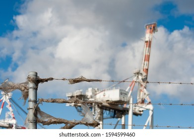 Fremantle, Western Australia - April 19, 2019: Plastic rubbish stuck on barbed wire fence with two heavy cranes in background