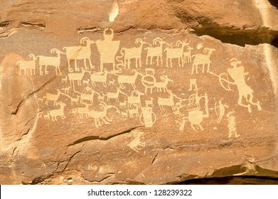 Fremont Indian hieroglyph in Nine Mile Canyon (near Price, Utah) featuring hunters with bows and arrows, a horned shamanic figure, and a shield figure in the middle of the bighorn sheep.