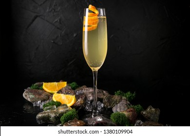 French 75 refreshing alcoholic beverage based on champagne, gin and sugar syrup on a black background with stones and ice. Cocktail card for a bar or restaurant.