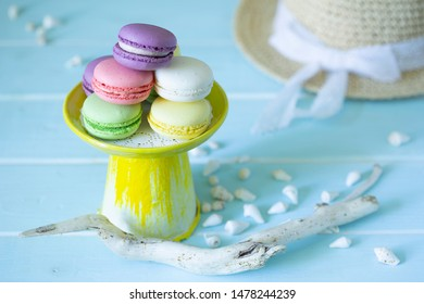 French almond cookies macaroons on yellow tray in marine decoration of shells, driftwood and sunhat on wooden blue background.