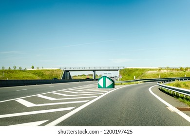French autoroute highway exit on the right with security differentiator and overpass - clear blue sky to great holidays