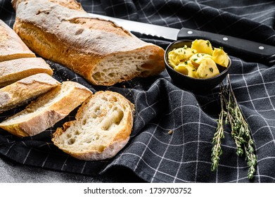 French baguette with butter for breakfast. black background. top view