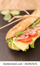 French baguette sandwich with cheese, ham, tomato, radish and lettuce.