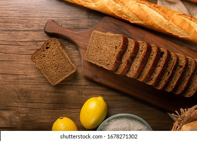 French baguette with slices of brown bread and lemons