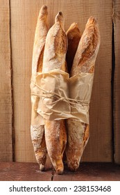 French baguettes in paper on wooden background