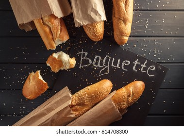 """French baguettes with sesame seed in paper bags and black chalkboard with inscription """"baguette"""" on black wooden background"""