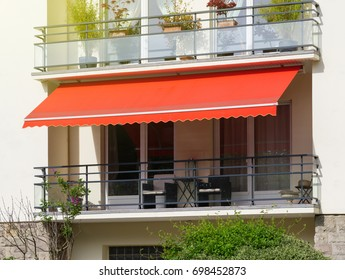 French balcony with awning opened covered by sun-shield on a warm summer day