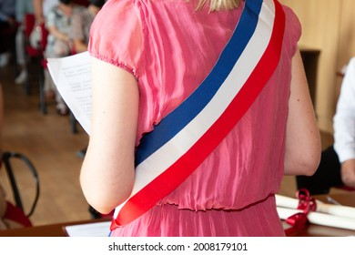 Femme blonde française maire avec foulard, tricolore du drapeau français et robe rose fille lors d'une fête officielle à la mairie de France