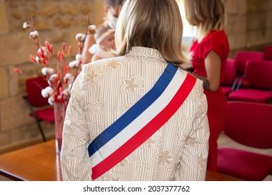 Femme blonde française maire avec foulard, tricolore du drapeau de la france et robe rose lors d'une fête officielle à l'hôtel de ville