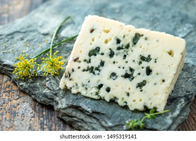 French blue cheese Roquefort, made from sheep milk in caves of Roquefort-sur-Soulzonwith grapes on grey stone